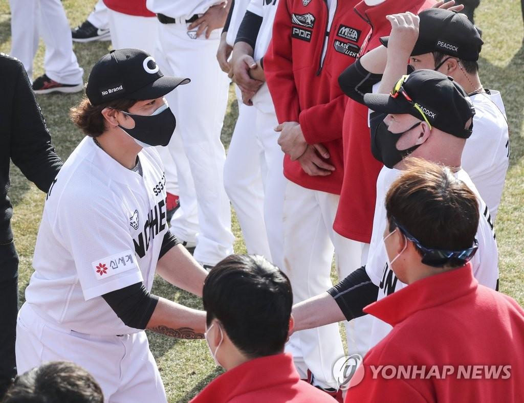 Choo Shin-soo of the SSG Landers (L) shakes hands with his teammate Jamie Romak at Sajik Stadium in Busan, 450 kilometers southeast of Seoul, on March 11, 2021. (Yonhap)