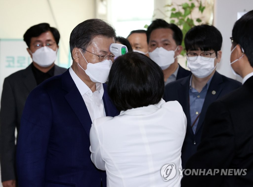 President Moon Jae-in gets his temperature checked upon arriving at the Jongno-gu public health center in Seoul for an AstraZeneca COVID-19 vaccine shot on March 23, 2021. (Yonhap)