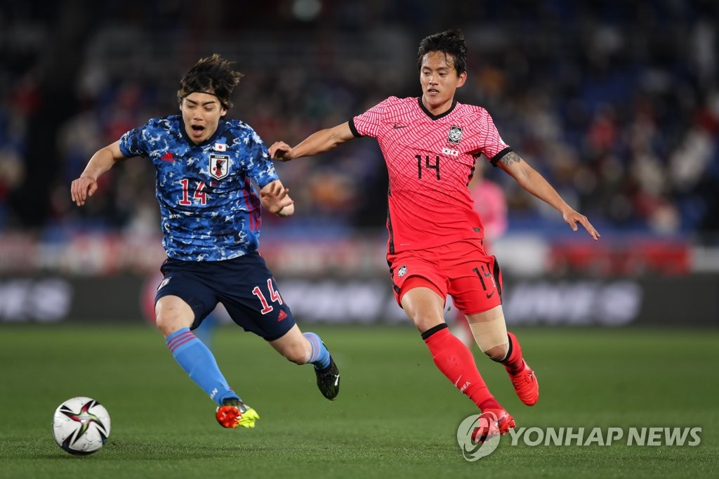 Hong Chul of South Korea (R) battles Junya Ito of Japan for the ball during their friendly football match at Nissan Stadium in Yokohama, Japan, on March 25, 2021, in this photo provided by the Korea Football Association. (PHOTO NOT FOR SALE) (Yonhap)