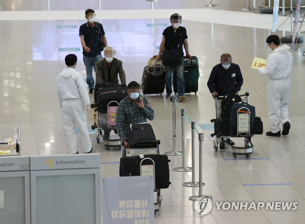 Travelers walk in an arrival hall of Incheon International Airport, west of Seoul, on April 6, 2021. (Yonhap)