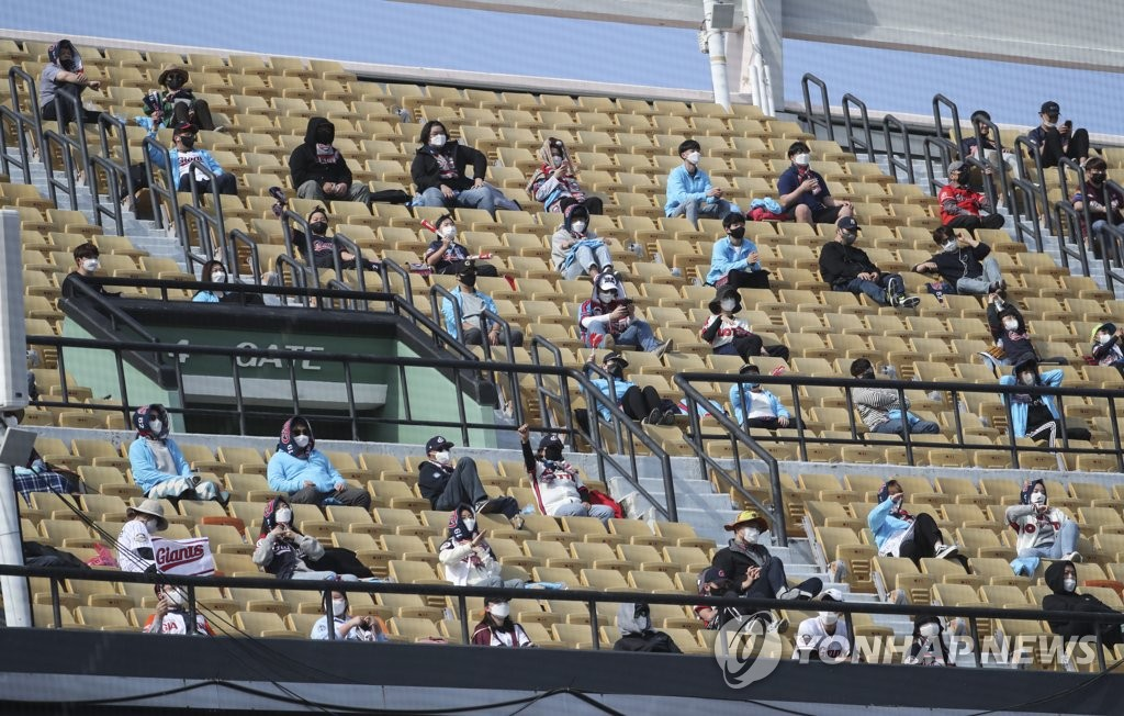 Spectators watch a baseball game while keeping a distance from one another at a stadium in the southeastern city of Busan on April 11, 2021. (Yonhap)