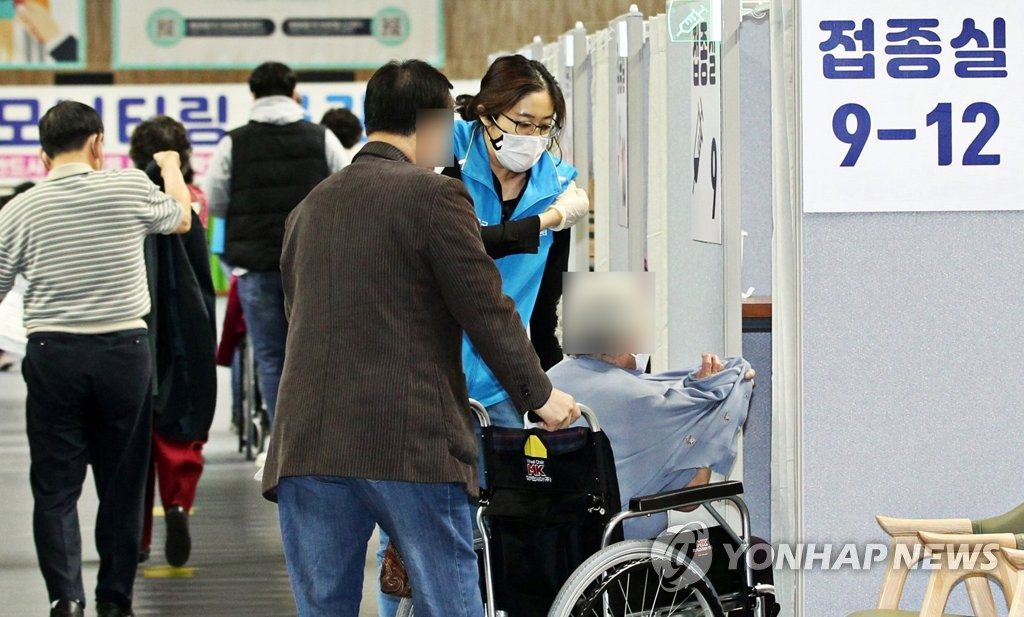 A senior in a wheelchair gets ready for inoculation with Pfizer's COVID-19 vaccine at a vaccination center in southern Seoul on April 17, 2021, in this photo provided by the Dongjak Ward Office. (PHOTO NOT FOR SALE)