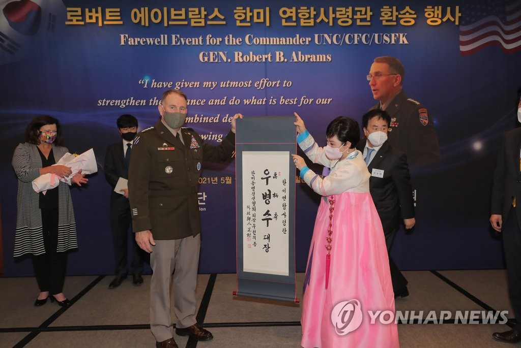 """Outgoing U.S. Forces Korea Commander Gen. Robert Abrams (L) receives a Korean name, Woo Byung-soo, as a gift from a South Korea-U.S. friendship group for his """"contribution to the alliance and defense of South Korea"""" during a farewell event in Seoul on May 13, 2021. (Yonhap)"""