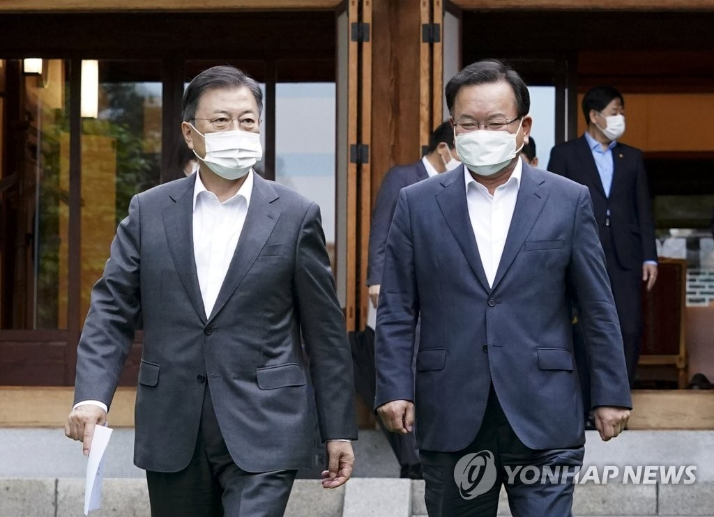 President Moon Jae-in (L) and Prime Minister Kim Boo-kyum walk together at a complex at Cheong Wa Dae in Seoul after holding their first regular weekly meeting on May 17, 2021, since Kim's inauguration last week. (Yonhap)