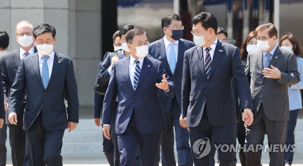 President Moon Jae-in (2nd from L, front) talks with Song Young-gil, head of the ruling Democratic Party, at Seoul Air Base in Seongnam, south of Seoul, on May 19, 2021. (Yonhap)