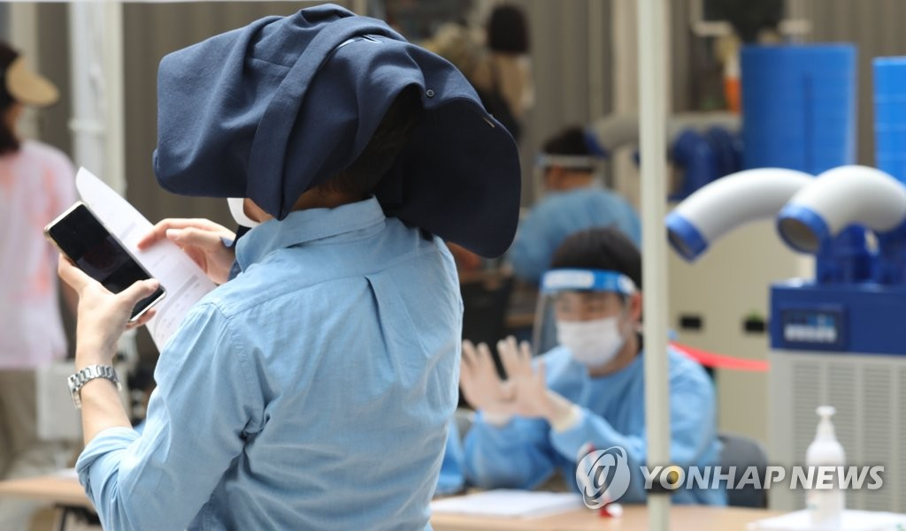 A citizen covers his head with his jacket to avoid sunlight as he waits in a line to receive COVID-19 tests in central Seoul on July 14, 2021. (Yonhap)