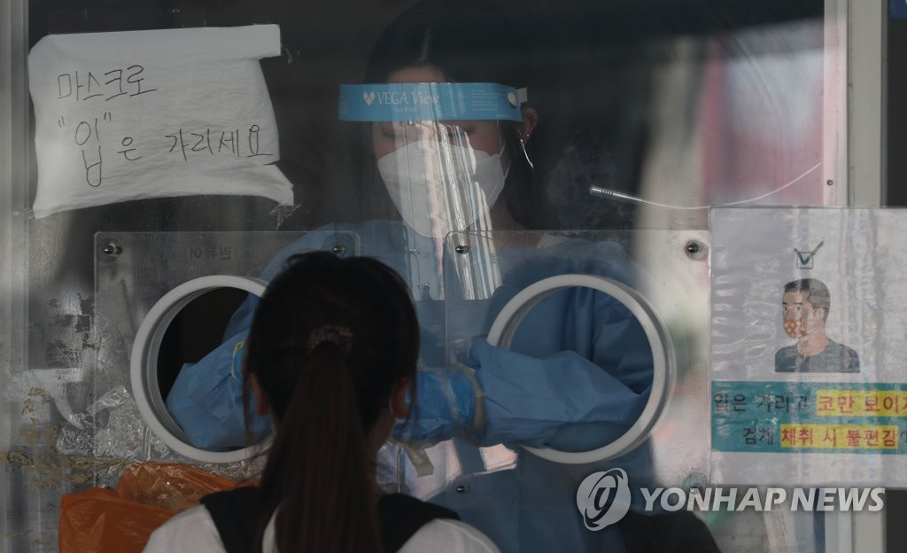 A health worker in protective gear collects a sample from a citizen at a makeshift virus testing clinic in Seoul on July 28, 2021. (Yonhap)