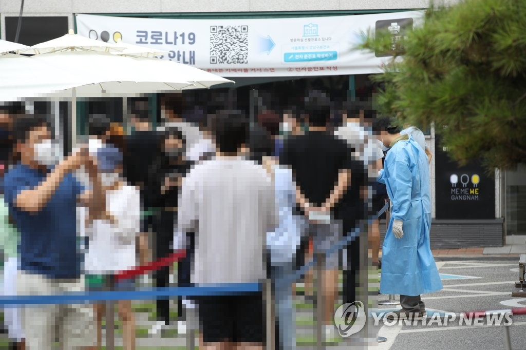 People wait in line to receive COVID-19 tests at a makeshift virus testing clinic in Seoul on July 30, 2021. (Yonhap)