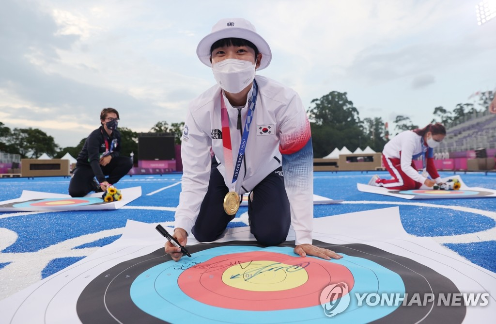 An San of South Korea signs the commemorative archery target after winning gold in the women's individual archery event at the Tokyo Olympics at Yumenoshima Park Archery Field in Tokyo on July 30, 2021. (Yonhap)